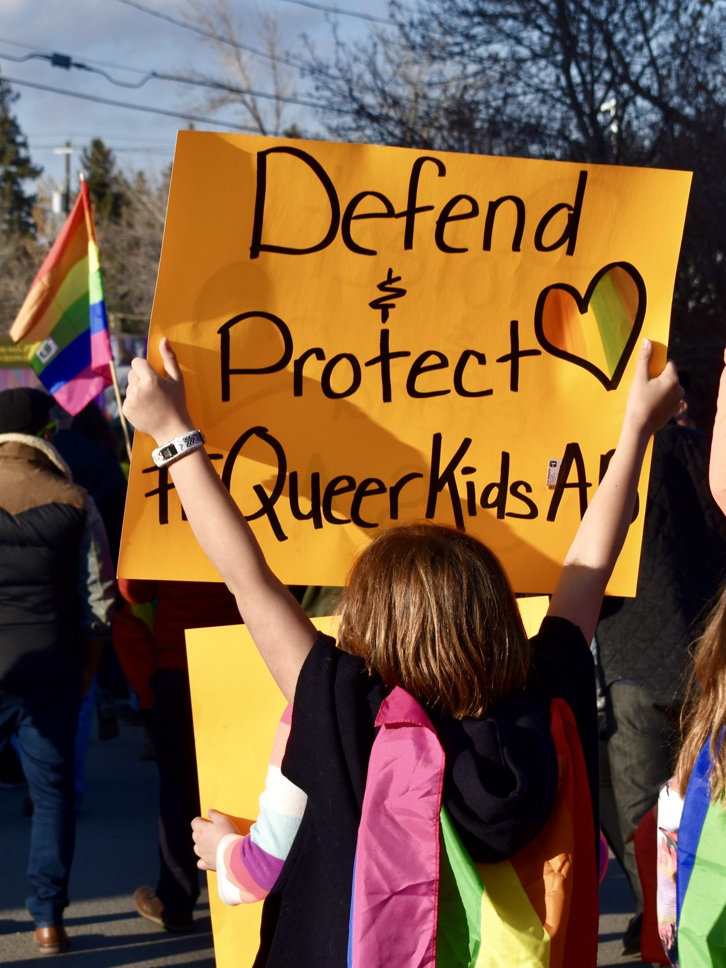 "A kid holding a sign that reads ""Defend and protect queer kids"""