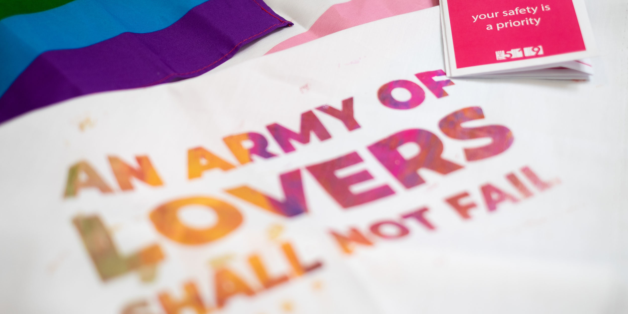 """Photo of a bandana that reads """"an army of lovers shall not fail"""" with the pride flag and trans flag in the background."""